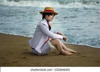 Cosplay de niño niña con sombrero de paja sentarse en la playa de arena cerca del mar de agua