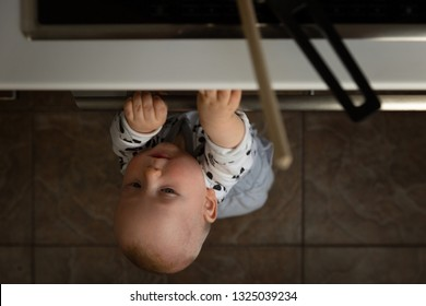 Little child playing with electric stove in the kitchen while sitting in highchair. Baby safety in kitchen