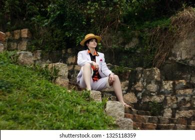 Cosplay des Jungenmädchens mit Strohhut sitzen auf Treppe / Steintreppe
