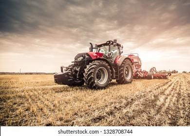 Moderner roter Traktor, der mit roter Ausrüstung unter Verwendung von GPS für die Präzisionslandwirtschaft auf den Feldern der Tschechischen Republik direkt in die Stoppeln sät.