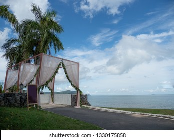 Wedding arch cover by white cloth and green leaves at beautiful beach with blue sky and nice weather.