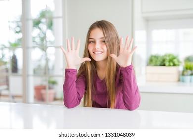 Niño hermoso joven en la mesa blanca mostrando y apuntando hacia arriba con los dedos número diez mientras sonríe confiado y feliz.