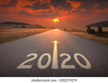 Fahren Sie auf einer idyllischen offenen Straße gegen die untergehende Sonne bis zum kommenden neuen Jahr 2020. Konzept für Erfolg und Zukunft.