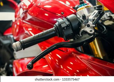 赤いオートバイのガスハンドルのクローズアップショット。