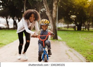 Niño lindo feliz aprender a andar en bicicleta con su madre. Madre enseñando a su hijo a andar en bicicleta en el parque.
