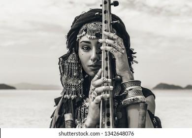 Hermosa mujer tribal con estilo joven en traje oriental tocando el sitar al aire libre. De cerca