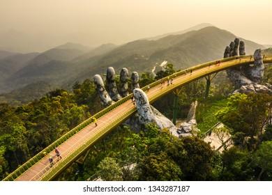 有名なゴールデンブリッジの空中写真は、ベトナムのダナンにあるバーナー山のツーリストリゾートで2つの巨大な手によって持ち上げられます。「カウヴァン」は観光客に人気の目的地です
