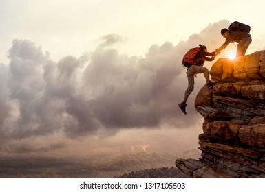 Menschen, die sich gegenseitig helfen, bei Sonnenaufgang einen Berg hinaufzuwandern. Eine helfende Hand geben und ein aktives Fit-Lifestyle-Konzept.