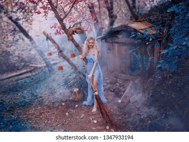 attractive blond lady sexy fairy in long light dress thin fabric with naked shoulder and open legs sweeps leaves with broom near little forest wooden house. curly witch vintage creative glamour style