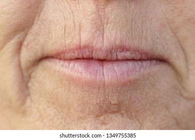 口を閉じて真面目な表情の中年ブルネット女性の口に極端なクローズアップ