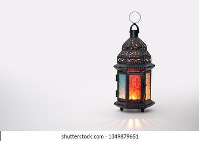 Arabische Zierlaterne mit brennender Kerze, die auf weißem Hintergrund glüht. Festliche Grußkarte, Einladung zum muslimischen heiligen Monat Ramadan Kareem.