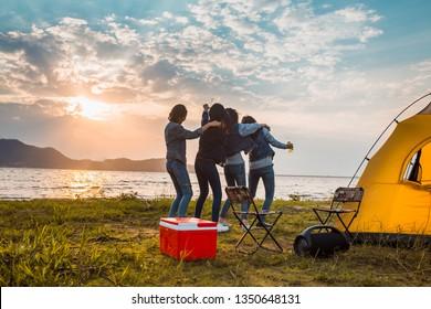 Groep vrouwen feesten en dansen met drankflessen genieten van reizen kamperen, wandelen in vakantietijd bij zonsondergang.