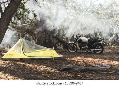 Camping en motocicleta con una bicicleta de estilo vintage en Mt Alexander, cerca de Bendigo, Victoria, Australia. Pequeña tienda de campaña, moto y humo.