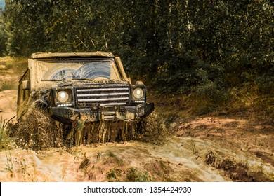 ジープは水たまりに衝突し、汚れのスプレーを拾いました。山の風景の間のオフロードスポーツトラック。泥の上を追跡します。4x4オフロードsuv車。オフロード車。サファリ。最高のオフロード車