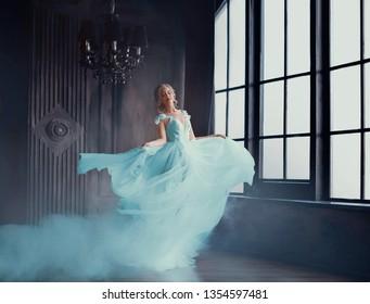 シンデレラが豪華なドレスを着た美しい王女に魔法のように変身します。若い女性は金髪で、暗くて暗い部屋で回転して踊っています。ドレスはその場で羽ばたきます。アート写真