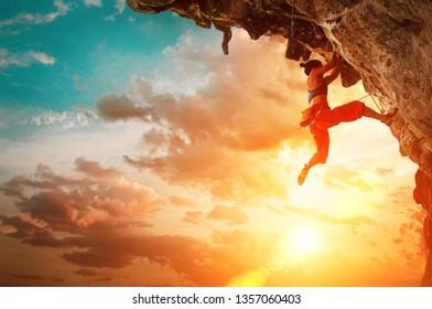 Sportliche Frau, die auf überhängendem Klippenfelsen mit Sonnenuntergangshimmelhintergrund klettert