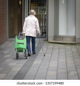 elderly woman with walking stick and green patterned shopping scooter goes to a double-winged door