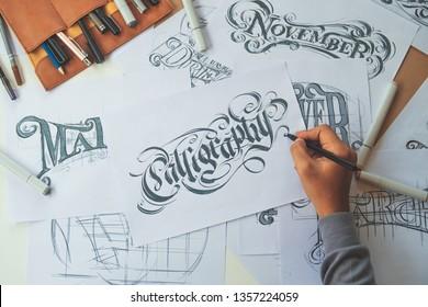 Typography Calligraphy artist designer drawing sketch writes letting spelled pen brush ink paper table artwork.Workplace design studio.