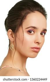 スタイリッシュな長いイヤリングを身に着けている、薄紫色のアイシャドウと濃い茶色の髪のきれいな女性のクローズアップの肖像画。アクセサリーは、モッキングジェイを眺めながらペンダントで飾られています。ハンガーゲームのシンボル。