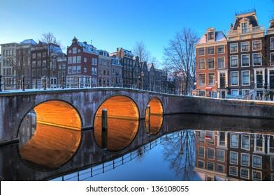 Wunderschöner Winterblick am frühen Morgen auf einem der UNESCO-Weltkulturerbe-Stadtkanäle von Amsterdam, Niederlande. HDR