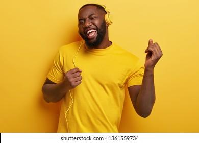 嬉しい暗い肌のふっくらとした男が踊り、音楽に合わせて動き、モダンなステレオヘッドホンを持ち、前向きに笑顔で元気になります。すべてが黄色です。のんきな男が生き生きとした音楽を聴く