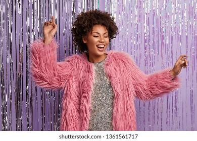 Inspirierte lockige Frau tanzt auf der Disco-Party, singt ein Lied, gekleidet in ein funkelndes Kleid und einen rosa Pelzmantel, hält die Hände hoch, genießt laute Musik während der Geburtstagsfeier und freut sich über eine gute Erholung