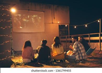 建物の屋上テラスで映画を見たり、ポップコーンを食べたり、ビールを飲んだり、楽しんだりする若い友人のグループ