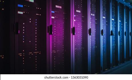 Disparo de Dark Data Center con múltiples filas de racks de servidores completamente operativos. Telecomunicaciones modernas, computación en la nube, inteligencia artificial, base de datos, supercomputadora. Luz de neón rosa.