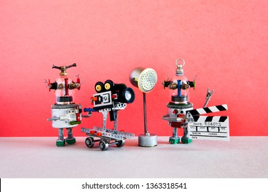 Funny robot cameraman and clapperboard assistant shoots dramatic comedy with elements of a horror movie and action adventure film. Motion picture robotic filmmaking backstage. The concept of automated