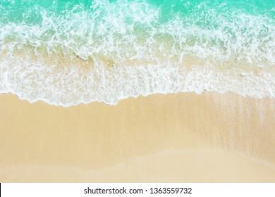Vare la orilla del mar de la arena con la onda azul y el fondo espumoso blanco del verano, playa aérea de la visión superior