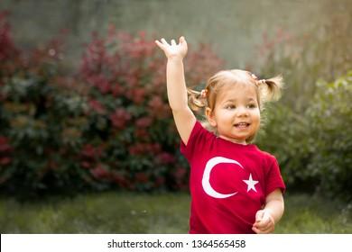 Porträt des glücklichen kleinen Kindes, des niedlichen Babykleinkindes mit türkischem Flaggen-T-Shirt winken ihre Hand. Patriotischer Urlaub. Entzückendes Kind feiert Nationalfeiertage. Hintergrund mit Kopierraum für Text verwischen.