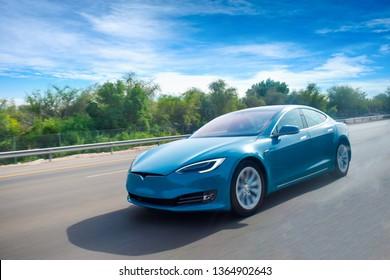Ein Elektroauto, das auf der Autobahn kreuzt, mit klarem blauen Himmel. Grünes Energiekonzept. Platz für Text.