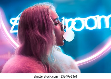 Young fashion teen girl in fur glasses blowing bubble gum illuminated with street neon blue pink sign, beautiful millennial woman in trendy night light glow back to 80s concept, profile side portrait