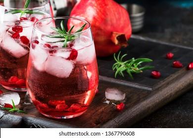 Roter Cocktail mit kaltem Wodka und Granatapfelsaft, Eiswürfeln und Rosmarin, Barwerkzeuge, blau-schwarzer Barthekenhintergrund, Kopierraum, selektiver Fokus