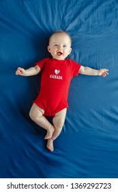 カナダの日にベッドに横になっている青い目をした白人の笑みを浮かべて男の子の女の子。7月1日、国民の祝日を祝う赤いワンピースロンパースの新生児の子供。上から見た図。クラシックブルー2020。