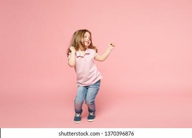 Pequeño niño lindo niño niña 3-4 años vistiendo ropa ligera bailando aislado sobre fondo de pared de color rosa pastel, retrato de estudio de los niños. Día de la Madre, familia del amor, concepto de infancia de la paternidad