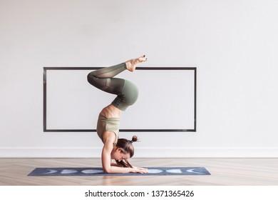 ジムのマットの上で逆立ちをしている柔軟な細い若い女の子の体操選手の側面図。アクロバットとサーカス俳優の概念。コピースペース