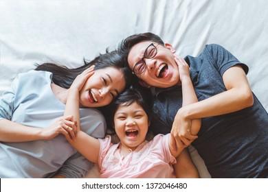 幸せと笑顔で寝室のベッドに横たわって幸せなアジアの家族、上面図