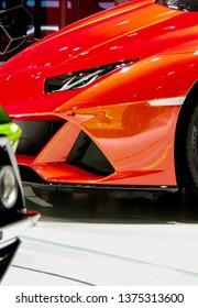 Orange sports car body headlight detail