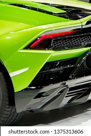 Shiny green sports car body tail light and exhuast pipe grid close up view