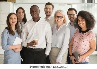 Motivierte internationale multiethnische Firmenmitglieder im Alter und im jungen Unternehmensteam, die für die Kamera posieren, erfolgreiches Mitarbeiterporträtkonzept des Wachstums in der Karriereführung und der Rassengleichheit