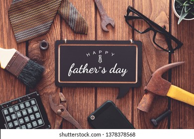 Happy father's day background concept. Flat lay of construction  handy tools and  gentleman's accessories over wooden background with black chalkboard and Happy father's day text.