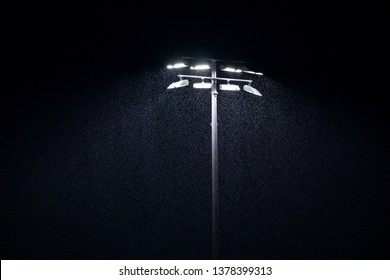 LED stadium lights at a rainy sports field, with a dark sky background, in a rain delay concept