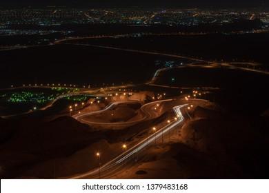 Nächtliche Langzeitbelichtung des Aussichtspunkts der verdrehten Autobahn auf Jebal Hafeet (auch bekannt als Jebel Hafit) mit Blick auf Green Mubbuzarah in Al Ain, Vereinigte Arabische Emirate.