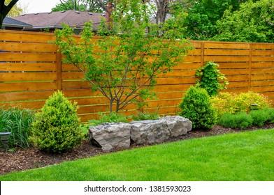 Un jardín de inspiración asiática y muy bien cuidado presenta rocallas y cercas de cedro de estilo minimalista.