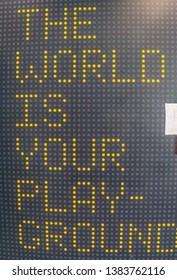 """""""De wereld is uw speelplaats"""" inspirerend citaat prikbord. Geel en zwart patroon display art. Motiverende slogan zin."""