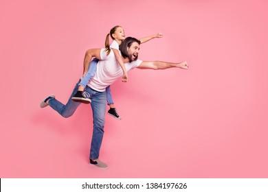Zijkant profiel lichaamsgrootte foto zij haar kleine dame hij hem zijn papa vader kleine prinses op de rug handen armen klaar vliegen dragen casual witte t-shirts denim jeans geïsoleerde roze achtergrond