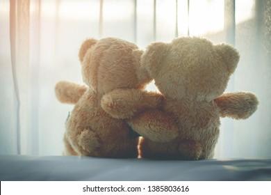 la parte trasera de la pareja ama la muñeca del oso en la habitación de la cama, se siente feliz y discreta. enfoque suave.