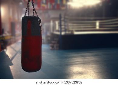 映画を撮るためにジムのボクシングのリングの前に赤いサンバッグがぶら下がっています