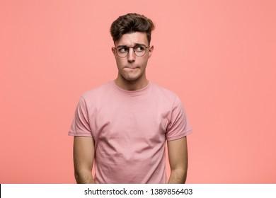 Joven hombre caucásico fresco confundido, se siente dudoso e inseguro.